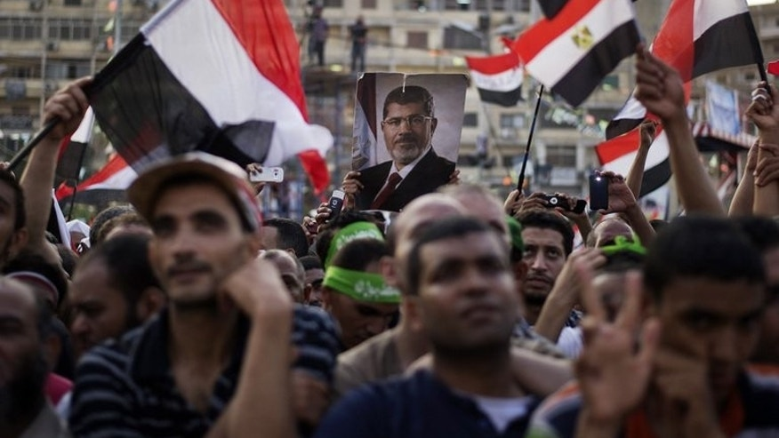 Supporters of deposed president Mohamed Morsi wave national flags during a rally outside Rabaa al-Adawiya mosque on July 15, 2013, in Cairo. Morsi's ouster has sparked a media war between the Arab world's major news rivals Al-Arabiya and Al-Jazeera over the policy lines of their respective funders in Riyadh and Doha.