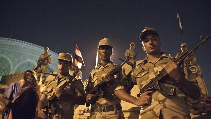 Egyptian soldiers stand in front of armoured vehicles outside the presidential palace in Cairo on July 19, 2013.