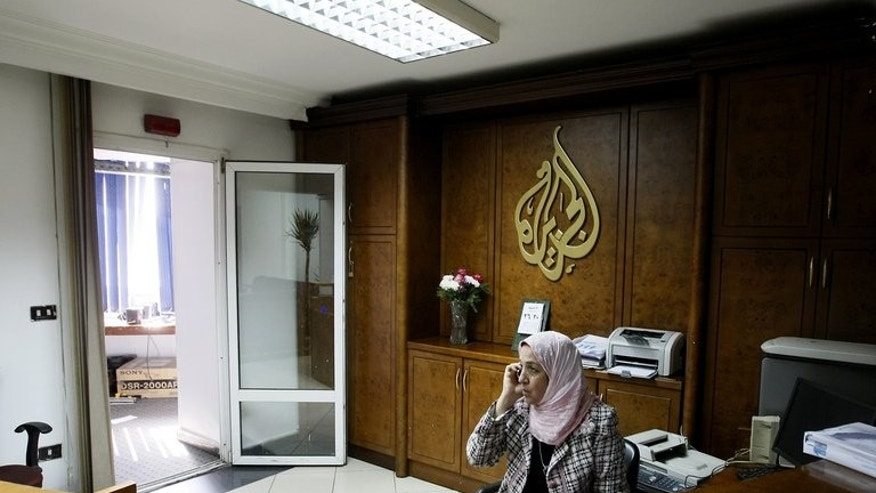 An Al-Jazeera employee talks on the phone at the pan-Arab television channel's bureau in Cairo on January 30, 2011.