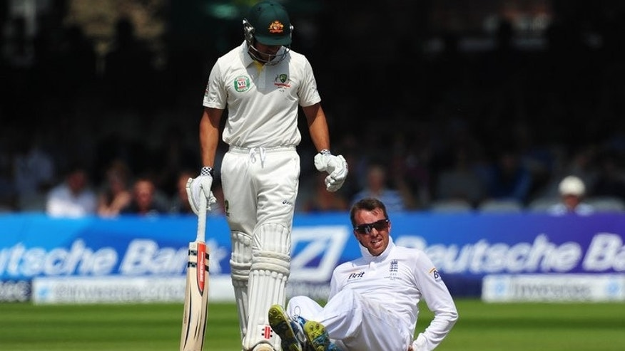 Australia's Usman Khawaja (L) collides with England's Graeme Swann whilst running between wickets during play on the fourth day of their second Ashes Test match, at Lord's cricket ground in north London, on July 21, 2013.