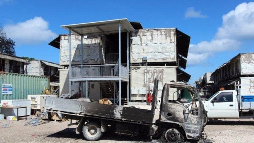 A burnt-out vehicle and destroyed accommodation blocks stand empty after riots at an Australian refugee facility on Nauru, July 20, 2013. Buildings were razed as hundreds of asylum-seekers rioted in protest at a new Australian immigration crackdown.