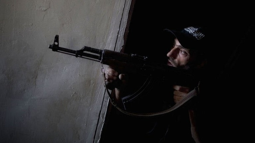 A Syrian rebel fighter points his gun towards pro-regime forces during clashes in the Salaheddine district of Aleppo, on July 9, 2013. Fighting is raging near Aleppo international airport and nearby air bases as the battle for Syria's second city enters its second year, according to the Syrian Observatory for Human Rights.