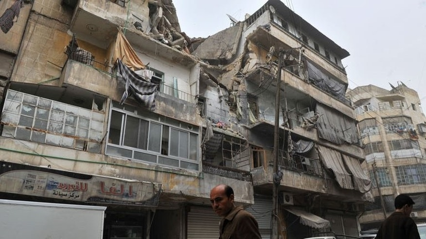 Syrians walk past a partially destroyed building in the northern city of Aleppo, on March 22, 2013. Fighting is raging near Aleppo international airport and nearby air bases as the battle for Syria's second city enters its second year, according to the Syrian Observatory for Human Rights.