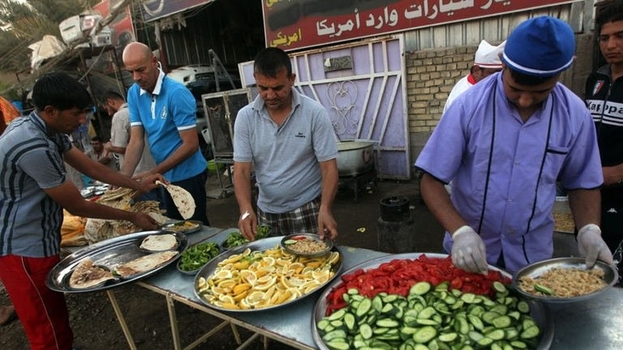 Iraqi Muslim men prepare food before breaking their fast during Ramadan, in Baghdad, July 17, 2013. Young Iraqis often spend evenings in cafes after fasting during the Muslim holy month of Ramadan, but a string of bombings against the popular hangouts means doing so now carries deadly risk.