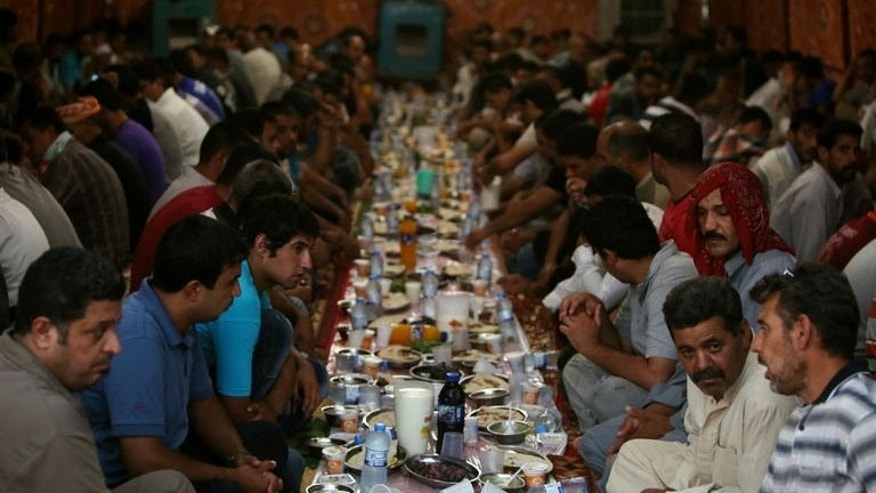 Iraqi Muslim men wait before breaking their fast, in a meal known as Iftar, inside a tent dedicated to cooking and eating during Ramadan in Baghdad, July 17, 2013.