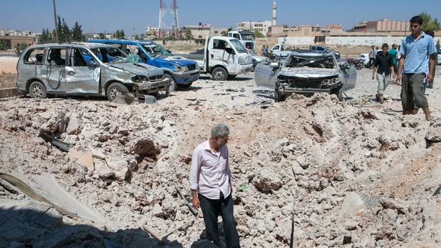 Syrians inspect the site where a barrel bomb dropped by an air force helicopter exploded in Saraqeb in northwestern Syria on July 20, 2013.
