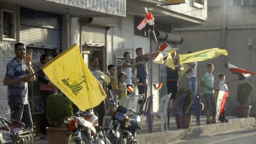 Residents of Qusayr in Syria's central Homs province wave their national flag and the flag of Lebanese Shiite Muslim party Hezbollah on June 5, 2013 as they celebrate after government forces seized total control of the former rebel-stronghold with the help of Hezbollah fighters