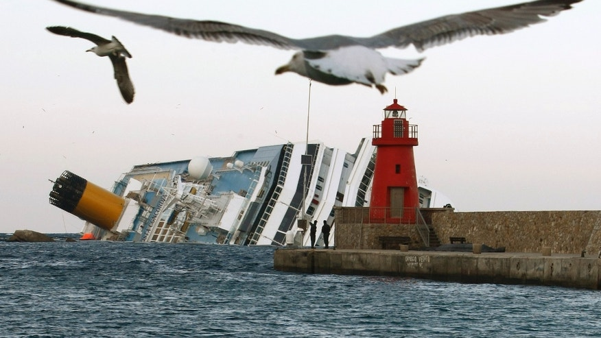 Seagulls fly in front of the grounded cruise ship Costa Concordia off the Tuscan island of Giglio, Italy, Monday, Jan. 30, 2012. Residents of Giglio are growing increasingly worried about threats to the environment and the future of the Italian island as bad weather again forced suspension of the recovery operation of the capsized cruise ship Costa Concordia. (AP Photo/Pier Paolo Cito)