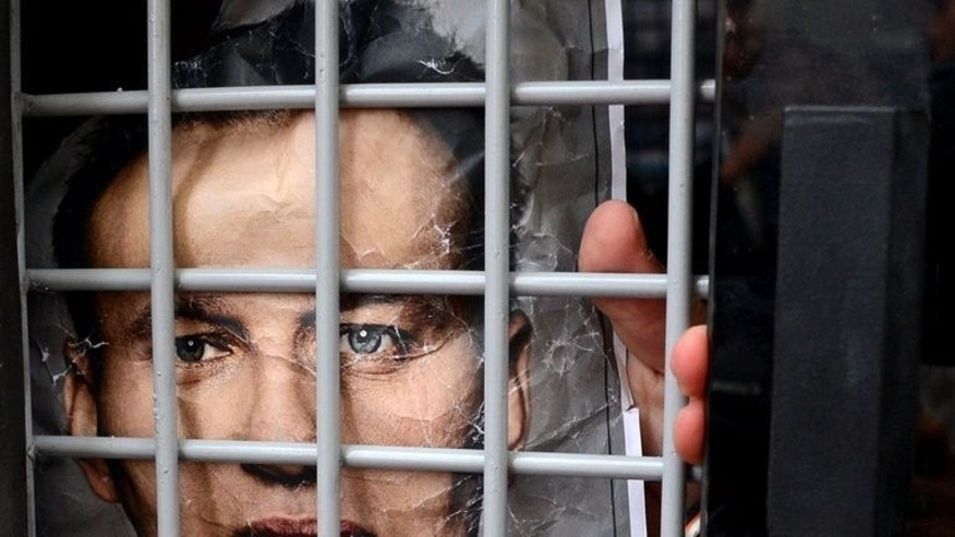 A protester detained by police during a demonstration in Moscow on July 18, 2013, holds a portrait of opposition leader Alexei Navalny. The Russian protest leader is preparing his campaign to challenge the pro-Kremlin elite in Moscow mayoral elections after returning home to a hero's welcome following his release from prison.
