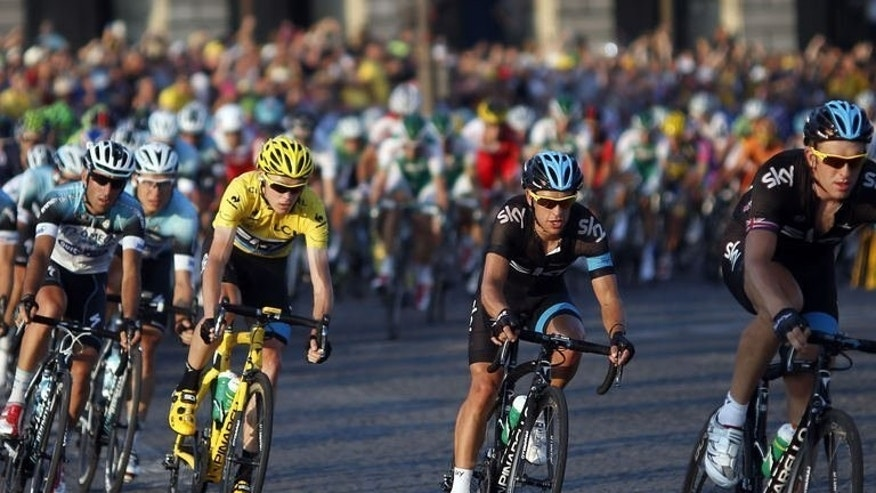 Britain's Christopher Froome rides in his yellow jersey behind team mates during the last stage of the Tour de France on July 21, 2013.