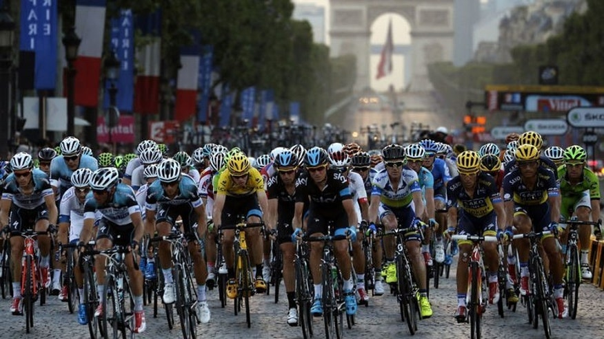 Overall leader's yellow jersey Britain's Christopher Froome and Spain's Alberto Contador (4th R) ride in the pack on the Champs Elysee avenue during the 133.5 km twenty-first and last stage of the 100th edition of the Tour de France cycling race on July 21, 2013 between Versailles and Paris.