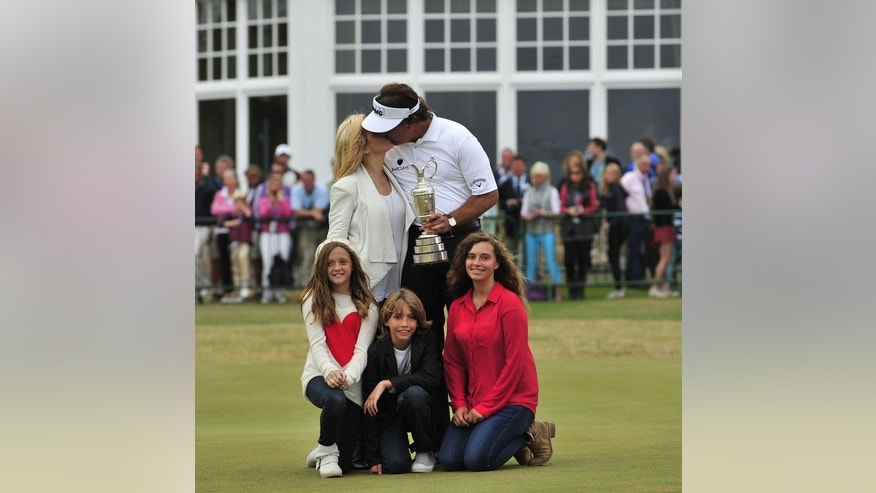 US golfer Phil Mickelson poses for pictures with his wife Amy (top L) and children Evan Samuel, Amanda Brynn and Sophia Isabel after winning the 2013 British Open Golf Championship at Muirfield golf course at Gullane in Scotland on July 21, 2013.