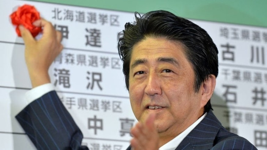 Japanese Prime Minister Shinzo Abe places a red paper rose on a Liberal Democratic Party candidate's name to indicate an election victory, at the party's headquarters in Tokyo, on July 21, 2013. Japan's ruling coalition has pledged it will push on with rebuilding the economy and turning the corner on two lost decades after securing a handsome majority in weekend upper house polls.