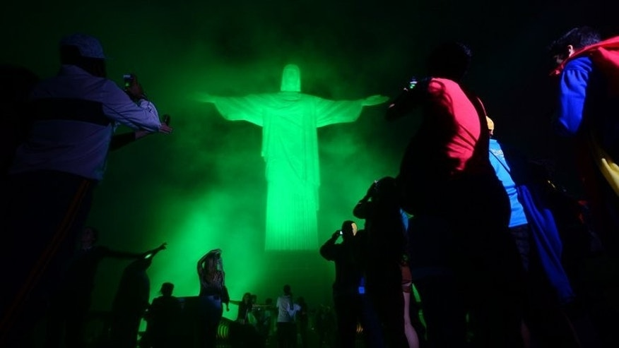 "Pilgrims take pictures of the Christ the Redeemer statue in Rio de Janeiro, Brazil on July 21, 2013. Bringing his message of a ""poor Church for the poor,"" Pope Francis heads to Brazil Monday to find a country facing a shrinking Catholic flock and anger over government waste."