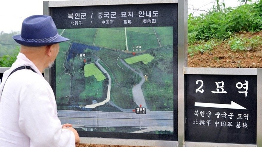 South Korean Buddhist monk Mukgai looks at a map of a military-controlled cemetery in Paju, for North Korean and Chinese soldiers who died during the 1950-53 Korean War near the heavily fortified border between the two Koreas, on May 29, 2013. Some 735 North Koreans and 369 Chinese are buried in the cemetery - the only one of its kind in S.Korea.