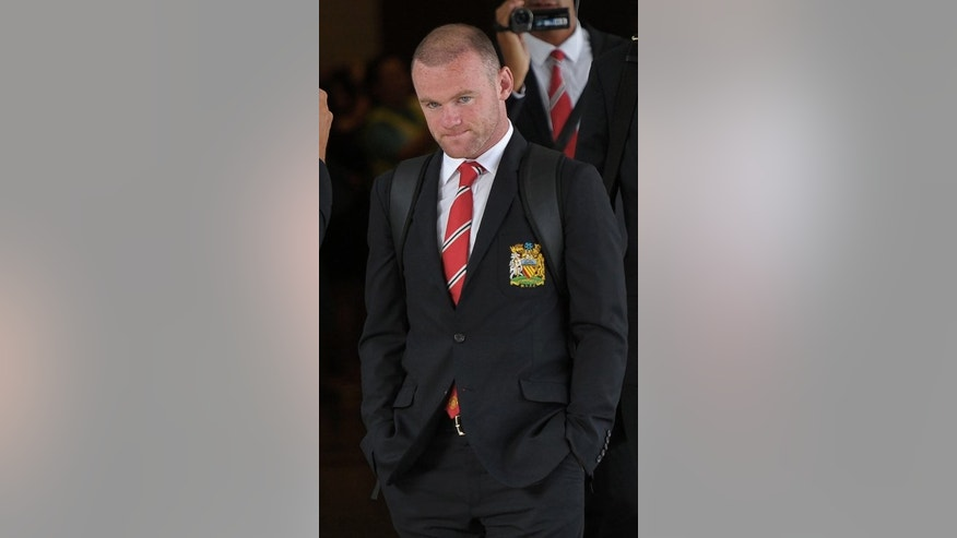 Manchester United player Wayne Rooney arrives at Don Muang International airport in Bangkok, July 11, 2013. Amid reports that Chelsea are considering a 40 million pound ($61 million) bid to land Rooney, the Premier League champions insist the England striker is not for sale.