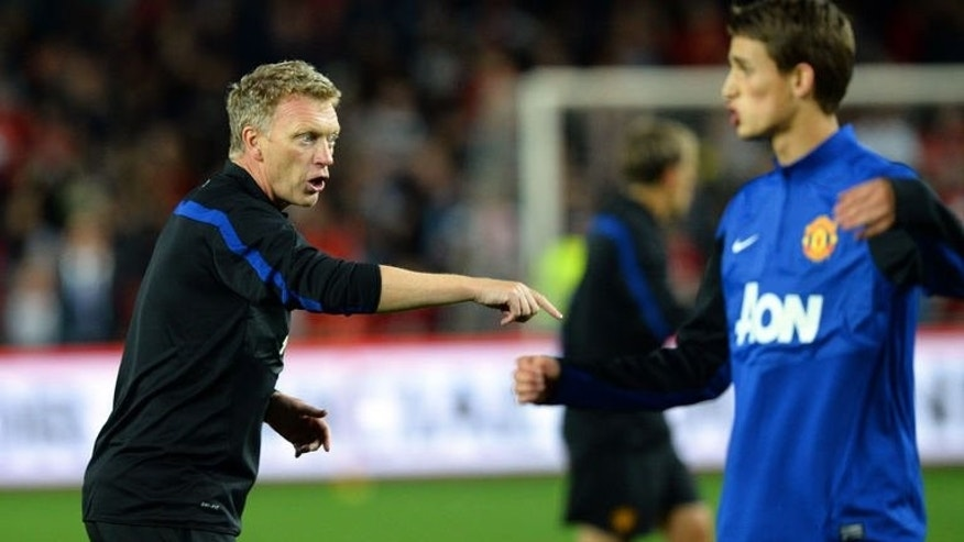 "Manchester United's Manager David Moyes (L) gives instructions to the players at the training session in Sydney on July 19, 2013. Moyes says he is looking forward to playing ""mind games"" with Jose Mourinho as Chelsea step up their interest in unsettled striker Wayne Rooney."