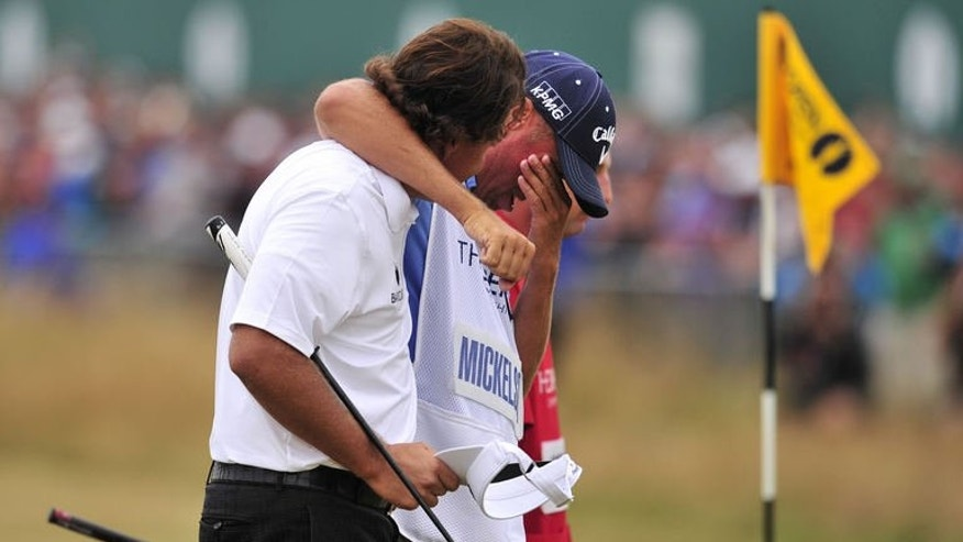 US golfer Phil Mickelson walks with his caddie Jim Mackay after scoring a birdie on the final 18th green during the fourth and final round of the 2013 British Open Golf Championship at Muirfield golf course at Gullane in Scotland on July 21, 2013.