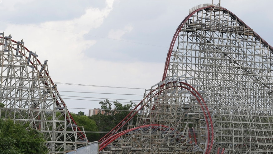 The Texas Giant roller coaster ride sits idle at the Six Flags Over Texas park Saturday, July 20, 2013, in Arlington, Texas. Investigators will try to determine if a woman who died while riding the roller coaster at the amusement park Friday night fell from the ride after some witnesses said she wasn't properly secured.(AP Photo/LM Otero )