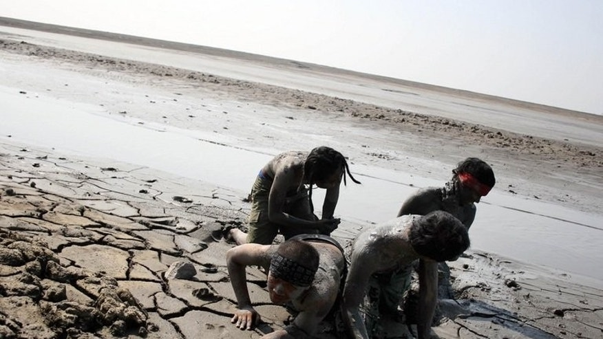 Indonesian activists cover themselves in sludge from a mud volcano during a protest in Porong village on May 29, 2011. Scientists have sparked a fresh debate over what triggered Indonesia's Lusi mud volcano, still spewing truckloads of slime more than seven years after it leapt catastrophically into life.