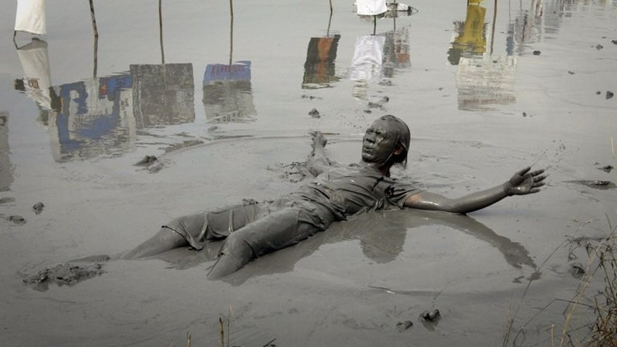 A displaced resident immerses himself in mud deposits during a protest in Sidoarjo village on Indonesia's Java island on May 29, 2013. A new study strengthens the argument by gas company PT Lapindo Brantas that the disaster was caused by a distant earthquake, not by its drilling crew as some experts contend.