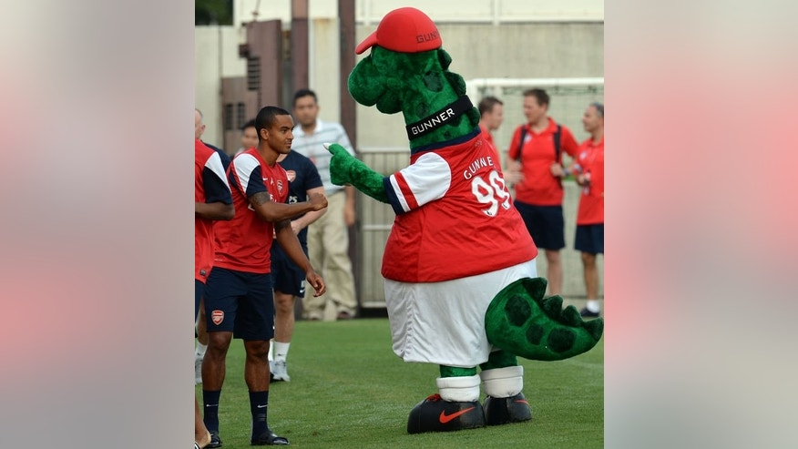 Arsenal forward Theo Walcott is greeted by the team's mascot Gunnersaurus Rex during a training session in Nagoya on July 21, 2013. Arsenal's Japanese leg of their pre-season Asian tour is a trip down memory lane for Arsene Wenger, as he faces former club Nagoya Grampus -- coached by one of his ex-players. AFP PHOTO / TOSHIFUMI KITAMURA
