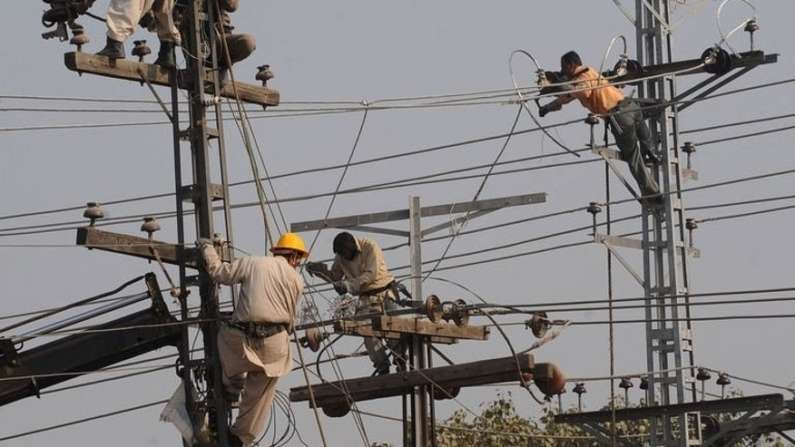 Technicians are seen working on high voltage power lines in Lahore, on January 13, 2011. A Pakistani power company is appealing to its customers' religious consciences in a desperate bid to get them to stop stealing electricity -- a major hurdle in efforts to stem crippling blackouts.