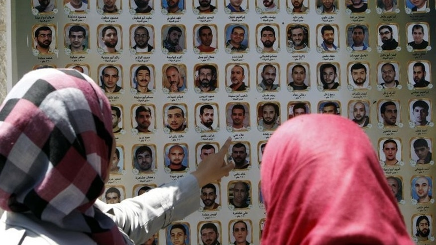 """Women look at images of jailed Palestinians during a rally outside the Red Cross offices in east Jerusalem, on July 6, 2011. Israel says it will release some Palestinian prisoners as a """"gesture"""" after the two sides agreed to resume peace negotiations. A US announcement that Middle East peace talks are to resume has been met with a wall of scepticism from Israeli officials and commentators."""