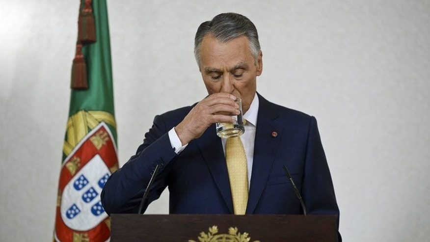 Portuguese President Anibal Cavaco Silva takes a drink as he addresses the nation from Belem Presidential palace in Lisbon on July 21, 2013. Cavaco Silva voiced support for the country's centre-right coalition government and rejected calls for snap elections to resolve a political crisis shaking the bailed-out nation.