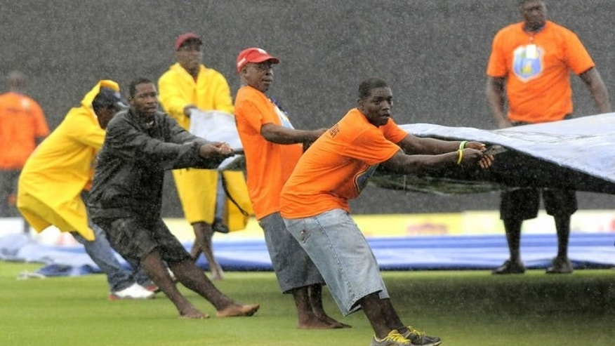 Ground staff struggle to pull covers in place at the start of the 4th one-day internatioanl between West Indies and Pakistan on July 21, 2013 in Gros Islet, St. Lucia.