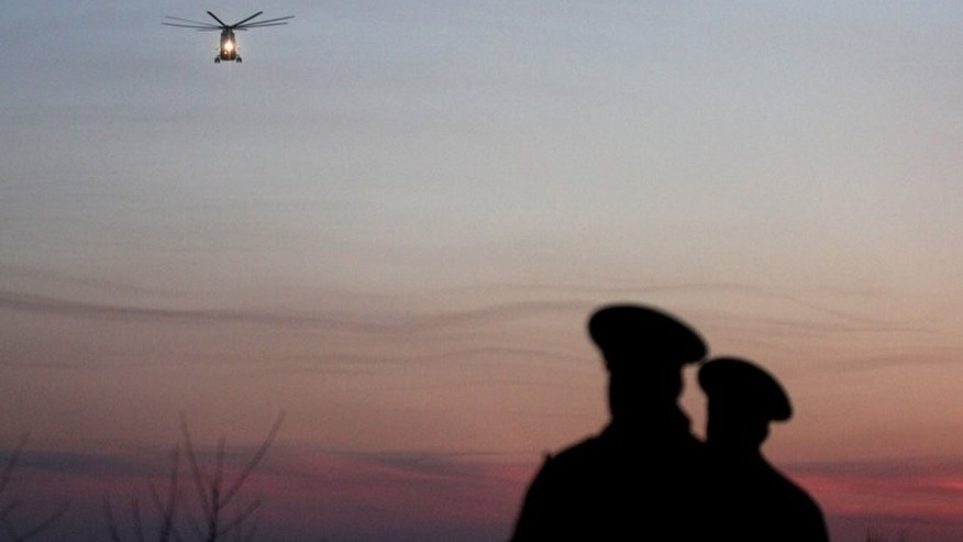 Two Russian policemen look at a helicopter. At least three people, including two British citizens, were killed in Russia's Far North when a helicopter crashed into them while they were standing on the ground, officials said.