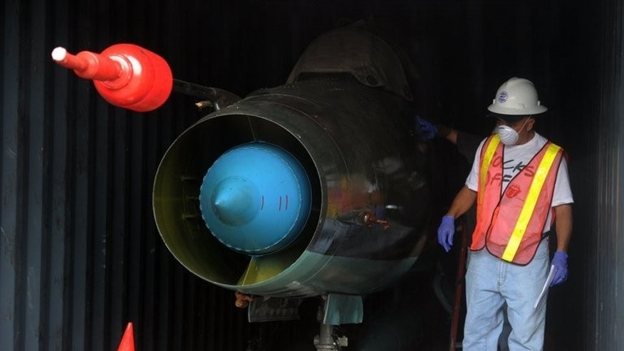 A man looks at a MIG-21 jet found inside a container on the North Korean Chong Chon Gang vessel seized at Manzanillo Port, Panama, on July 21, 2013. Panamanian authorities have found two Soviet-era MiG-21 fighter jets aboard the North Korean ship.