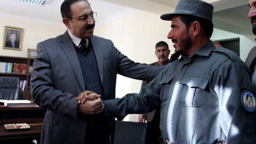 Afghanistan's Interior Minister Mujtaba Patang (left) speaks with a police officer in Kabul, on December 25, 2012. Afghanistan's parliament has sacked Patang -- one of the country's most powerful security chiefs -- less than a year after he took office.