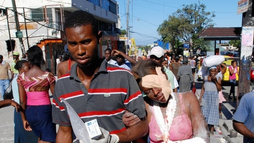 An injured woman is helped after being rescued on January 13, 2010 in Port-au-Prince, Haiti.