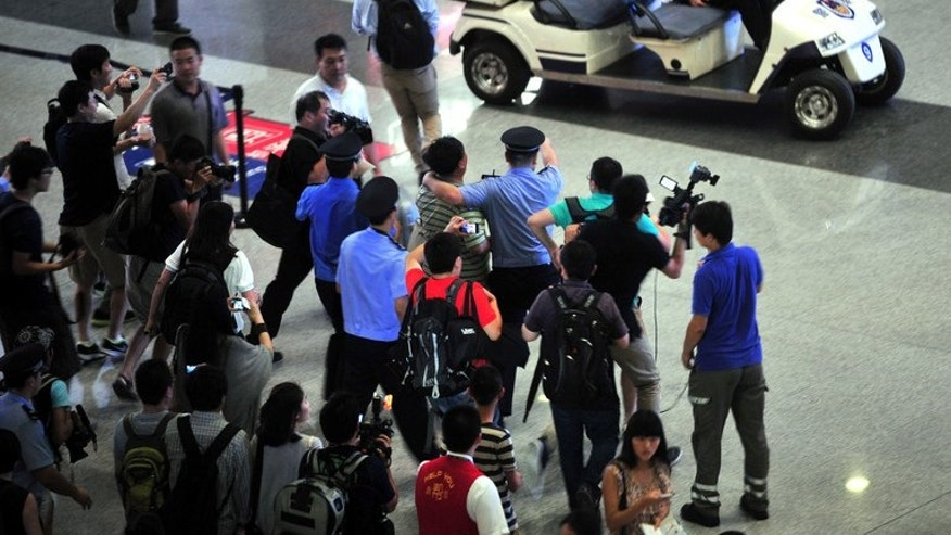 Security personnel hold back reporters from getting closer to the scene where a man in a wheelchair ignited a home-made explosive device at Beijing's international airport terminal 3, on July 20, 2013, injuring himself but no others, in apparent protest against police brutality.