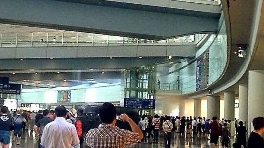 People leave Beijing's international airport Terminal 3 after a man in a wheelchair ignited a home-made explosive device, on July 20, 2013.