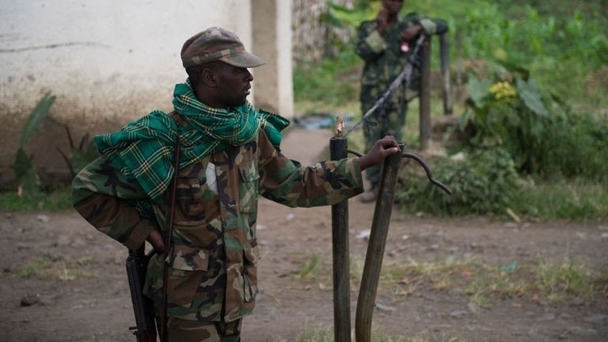 M23 rebels man the gate to the military academy in Rumangabo in the east of the Democratic Republic of Congo on July 20, 2013. Fresh fighting raged in the country's restive east for several hours as army helicopters attacked positions of the M23 rebels, who fired mortars in return.