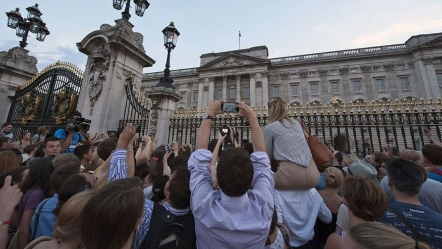 Camera flashes lit up the evening scene outside the queen's official residence as dozens of people tried to immortalise the moment it was announced that the third in line to the British throne had been born.