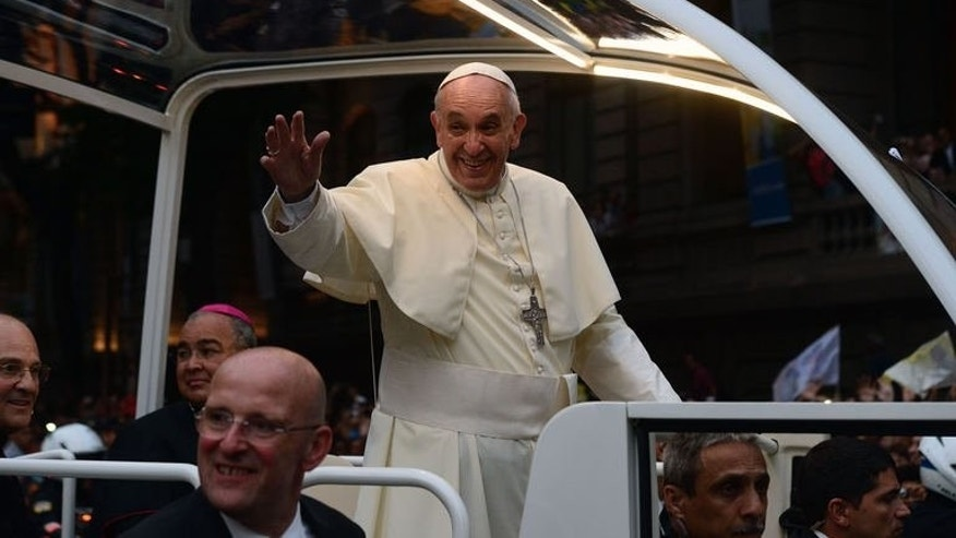 Pope Francis waves at faithfuls from the popemobile on his way to the Guanabara Palace after his arrival in Rio de Janeiro on July 22, 2013.