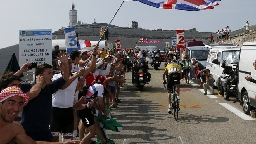 A supporter of British cyclist Chris Froome waves a Union Jack as the overall leader heads towards a win in the 15th stage of the 100th Tour de France between Givors and Mont Ventoux, southeast France on July 14, 2013. Kenya, birthplace of Tour de France winner Froome, celebrated his victory on Monday but expressed regret that it was Union Jacks and not Kenyan flags being waved across Paris.