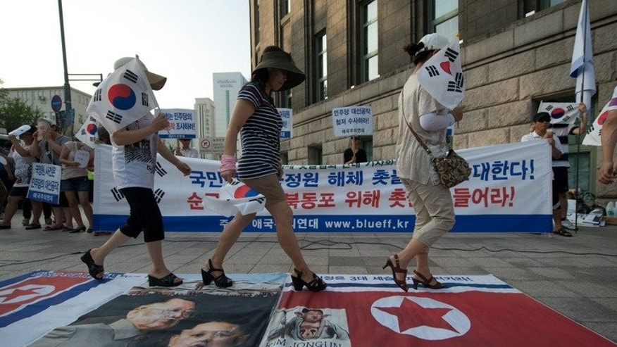 Protesters walk across a banner showing North Korean leader Kim Jong-Un and the late Kim Jong-Il in Seoul on July 6, 2013.
