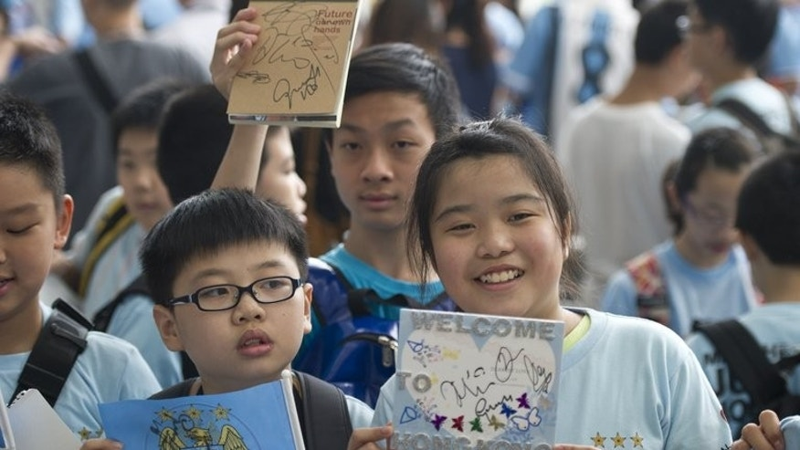 Young fans hold signed memorabilia after the arrival of English Premier League team Manchester City, in Hong Kong, on July 22, 2013. The big-spending FC touched down in the southern Chinese city after two losses in friendlies in South Africa.