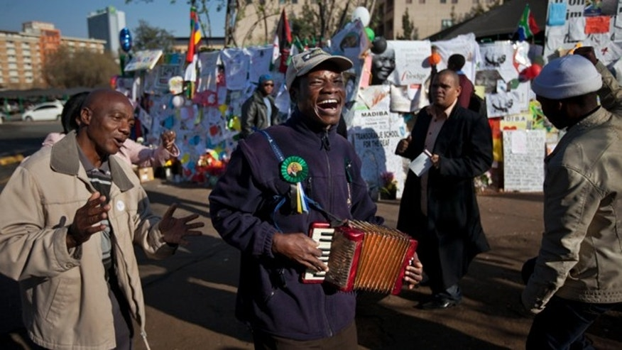 July 19, 2013: Well-wishers sing and dance to the sound of an accordion outside the Mediclinic Heart Hospital where former South African President Nelson Mandela is being treated in Pretoria, South Africa.