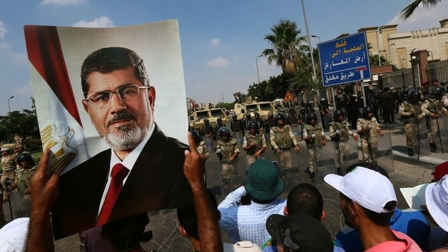 "A supporter of the Muslim Brotherhood raises a picture of Mohammed Morsi during a demonstration iin Cairo, on July 19, 2013. The family of Morsi is to take legal action against Egypt's army chief, General Abdel Fattah al-Sisi, for ""kidnapping"" the Islamist president, his daughter has told reporters in Cairo."
