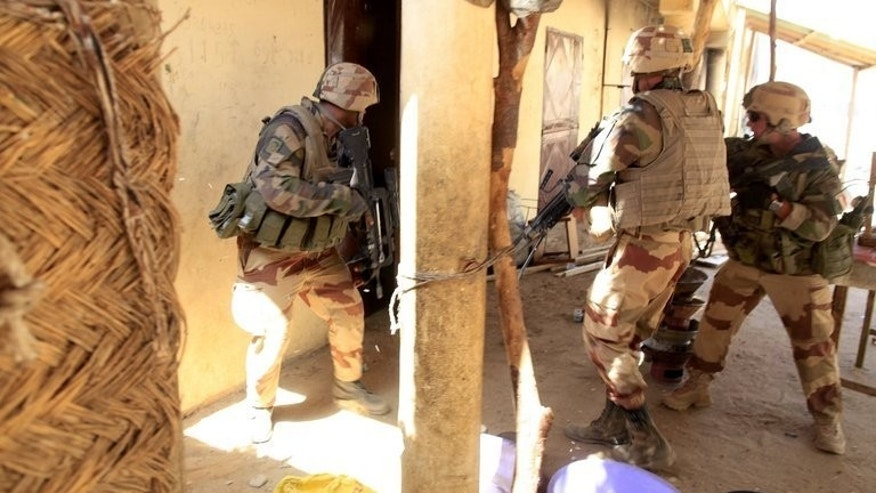 French soldiers search houses after clashes in the city of Gao on February 21, 2013. Mali is hoping against the odds for credible July 28 presidential elections but crucial barriers to an acceptable voter turnout and the ever-present threat of terrorist attacks are casting a long shadow over preparations.
