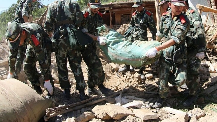 Rescuers work in the ruins of a damaged house in Hetuo township in Dingxi, northwest China's Gansu province on July 22, 2013. Rescuers battled through dusty rubble Tuesday to try to reach victims of two shallow earthquakes in China that killed at least 89 people.