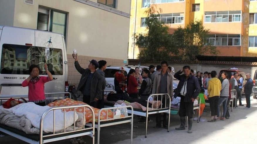 Injuried people lie on beds outside a hospital in Minxian after an eathquake hit the area in northwest China's Gansu province on July 22, 2013.