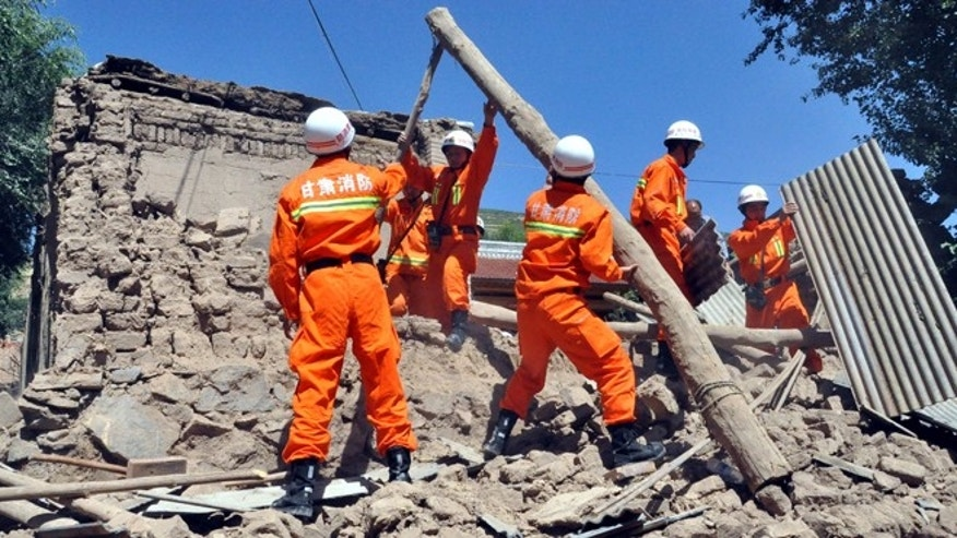 July 22, 2013: In this photo released by Xinhua News Agency, rescuers clear the debris of a damaged house in quake-hit Majiagou Village of Minxian County, northwest China's Gansu Province.