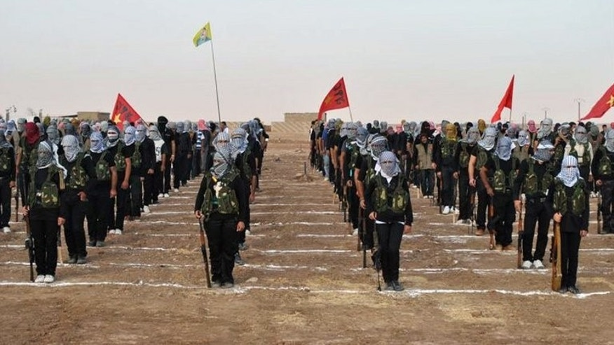 Kurdish fighters attend a ceremony on July 18, 2013, in the northern Syrian border village of al Qamishli. The Syrian Observatory for Human Rights said that Islamists battling Kurdish fighters in the northern town of Tal Abyad freed 300 Kurdish civilians they were holding prisoner in exchange for a rebel chief.