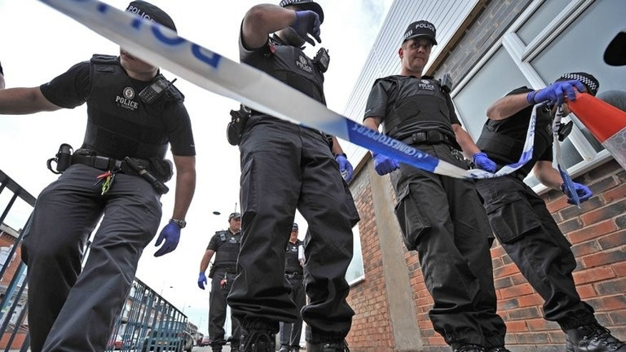 "Police officers search a crime scene in Birmingham on August 10, 2011. British police on Monday charged a Ukranian man with the ""terrorist-related"" murder of an elderly Muslim man who was walking home from a mosque."